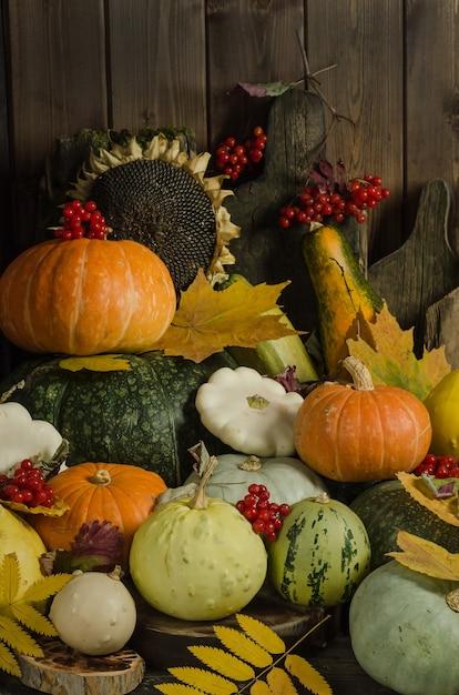 Тыквы, ягоды и осенние листья на старом деревянном столе Premium Фотографии