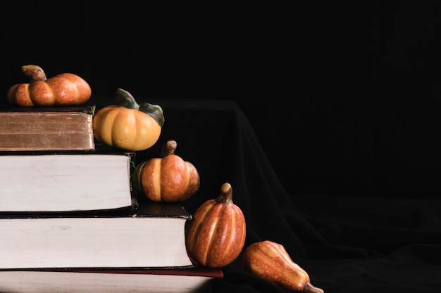 Pumpkins and books on black background Free Photo