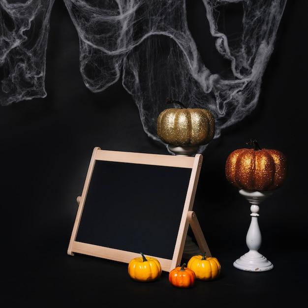 Zucche e lavagna vicino decorazioni di halloween Foto Gratuite