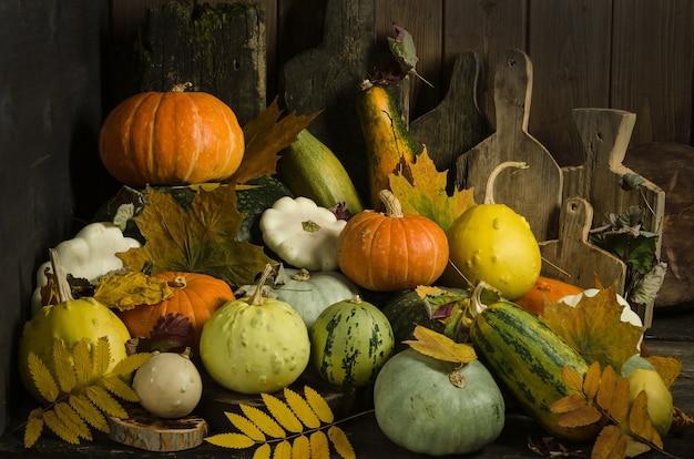 Тыквы, разделочные доски и осенние листья на старом деревянном столе Premium Фотографии