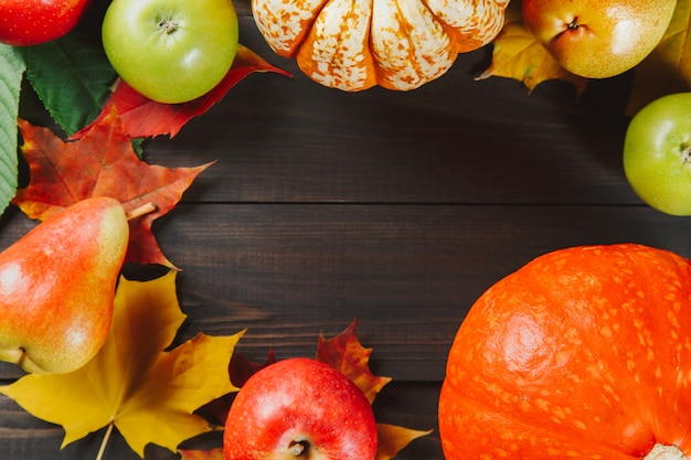 Pumpkins with colorful maple leaves, ripe apples and pear on dark wooden background Premium Photo