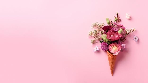 Конус мороженого с розовыми цветами и листьями на фоне punchy пастельных. Premium Фотографии