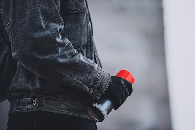 Панк в джинсовой куртке и черных перчатках принимает аэрозольную краску. новые субкультуры на городских улицах Premium Фотографии