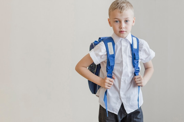 Pupil in backpack standing in studio Free Photo