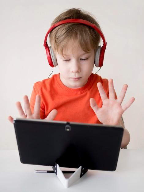 生徒が指で数えてウェブカメラに見せている 無料写真