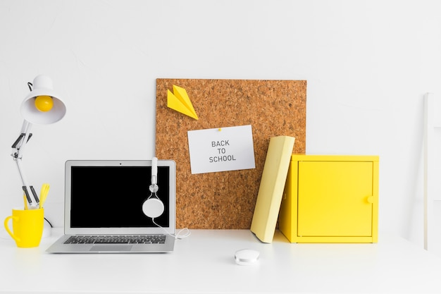 Pupil creative workplace with cork board and laptop Free Photo