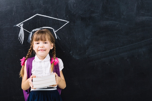 Pupil girl with books in master hat Free Photo