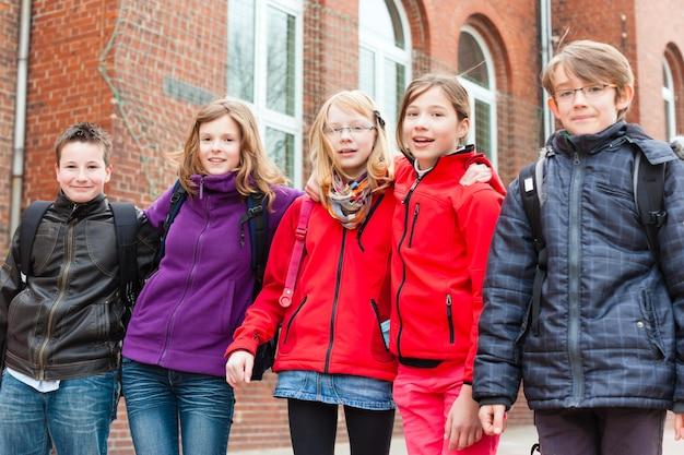 Ученики на школьном дворе своей школы Premium Фотографии