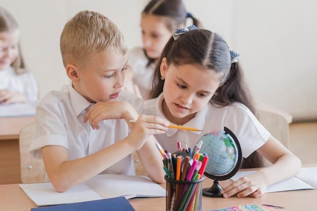 Ученики, смотрящие на глобус вместе Premium Фотографии