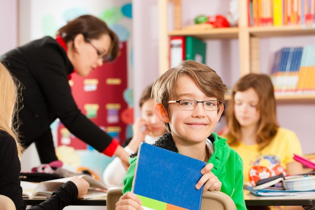 Pupils and teacher learning at school Premium Photo