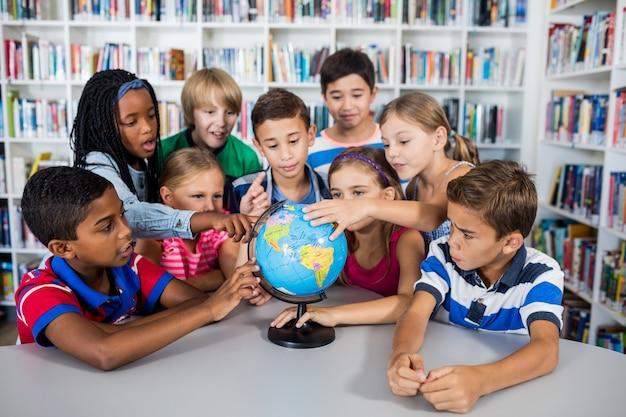Pupils touching globe Premium Photo