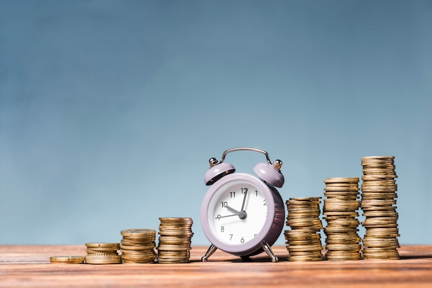 Purple alarm clock between the stack of increasing coins on wooden desk against blue background Free Photo