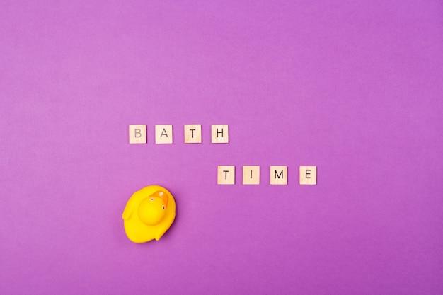 Фиолетовый фон с деревянными буквами bath time и резиновая желтая утка. вид сверху. квартира лежала. ванна тема тема ребенка. Premium Фотографии