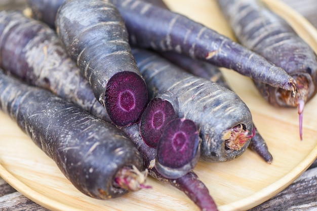Фиолетовая морковь на деревянной тарелке, свежая морковь для приготовления вегетарианских блюд на деревянном столе Premium Фотографии