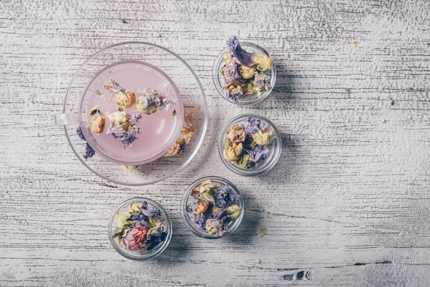 Вода фиолетового цвета в чашке с высушенным взгляд сверху чая цветка на белой деревянной предпосылке Бесплатные Фотографии
