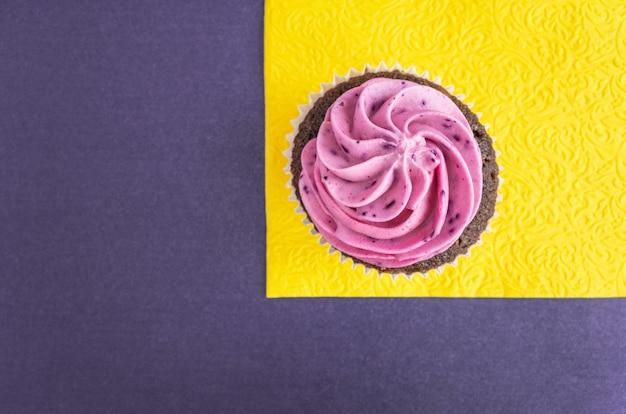 黄色のナプキンと青に紫のクリームカップケーキ Premium写真