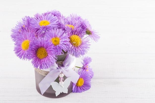 Purple daisies on white table Premium Photo