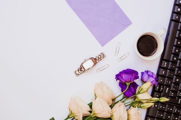 Purple envelope; wristwatch; paperclip; coffee cup; keyboard and eustoma flowers on white background Free Photo
