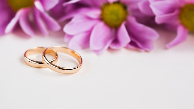 Purple flowers beside engagement rings Free Photo