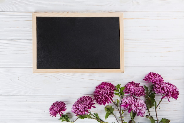 Purple flowers with blank chalkboard on white table Free Photo