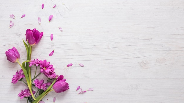 テーブルの上の花びらと紫の花 Premium写真