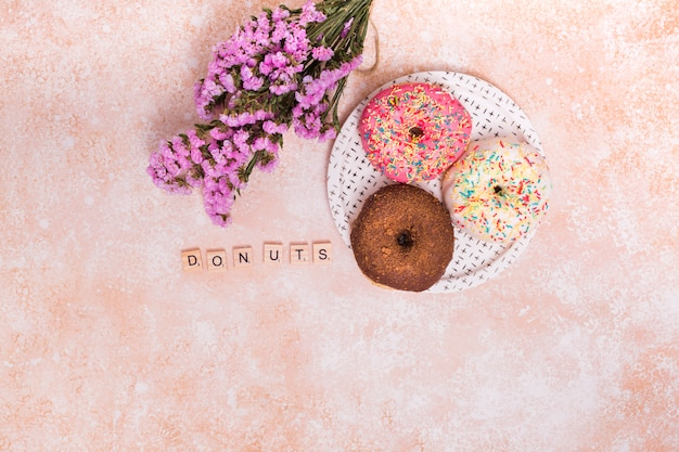 Purple gypsophila flowers; donuts blocks and baked donuts on plate over the rustic backdrop Free Photo