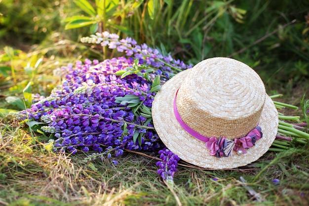 フィールドに麦わら帽子で覆われた紫色のルピナスの花。朝の草のルピナスの花の花束の近くの帽子。コンセプト夏のピクニック。麦わらの花で飾られた麦わら帽子。素朴なスタイルの家の装飾 Premium写真