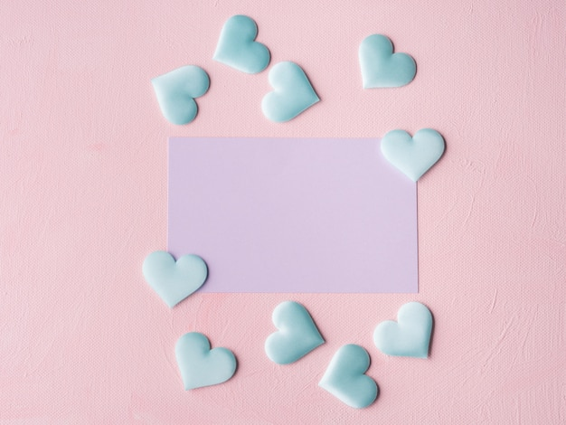 Purple pastel card and hearts on pink textured Premium Photo