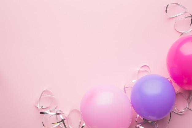 보라색, 분홍색 공 및 분홍색 종이 바탕에 은색 뱀. 휴일 배경. 공간 복사 프리미엄 사진