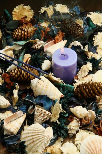 Purple potpourri with candle and pine cones Premium Photo
