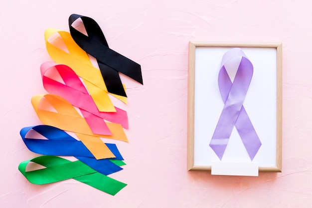Purple ribbon on white wooden frame with the row of colorful awareness ribbon Free Photo