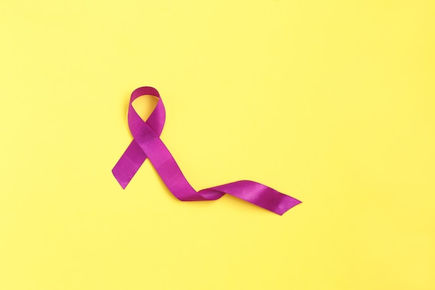 Purple ribbon on yelow background for cancer day Premium Photo