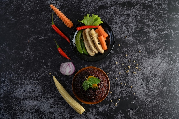 Purple rice berries cooked with grilled chicken breast. pumpkin, carrots, and mint leaves in a dish, clean food. Free Photo