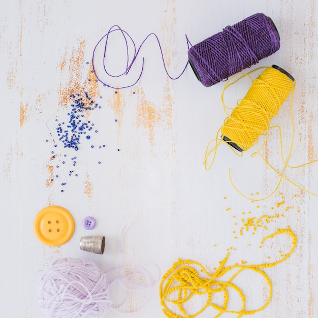 Purple and yellow yarn ball; button with beads on white wooden textured backdrop Free Photo