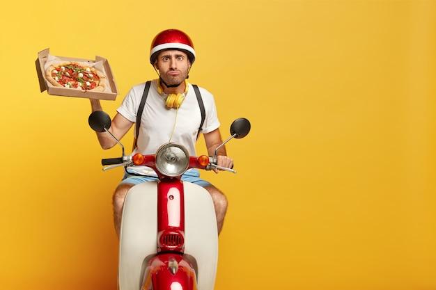 Autista maschio bello intenzionale su scooter con casco rosso che consegna pizza Foto Gratuite