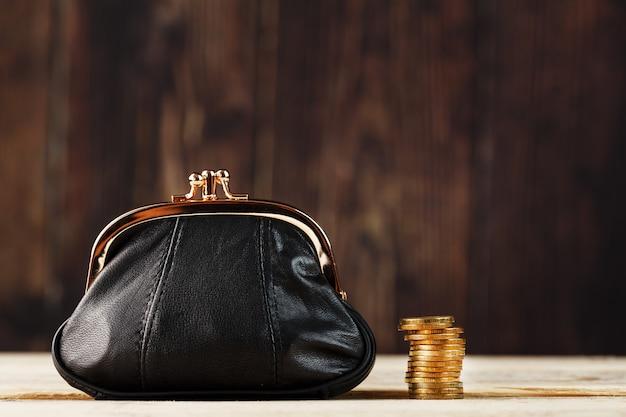 Кошелек с деньгами и на деревянный стол. бюджет для инвестиций в будущее. Premium Фотографии