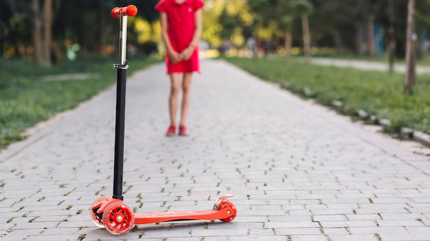 Push scooter in front of girl standing on walkway in the park Free Photo