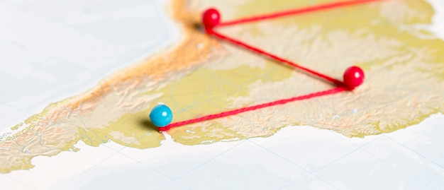 Pushpins with thread on route map Free Photo