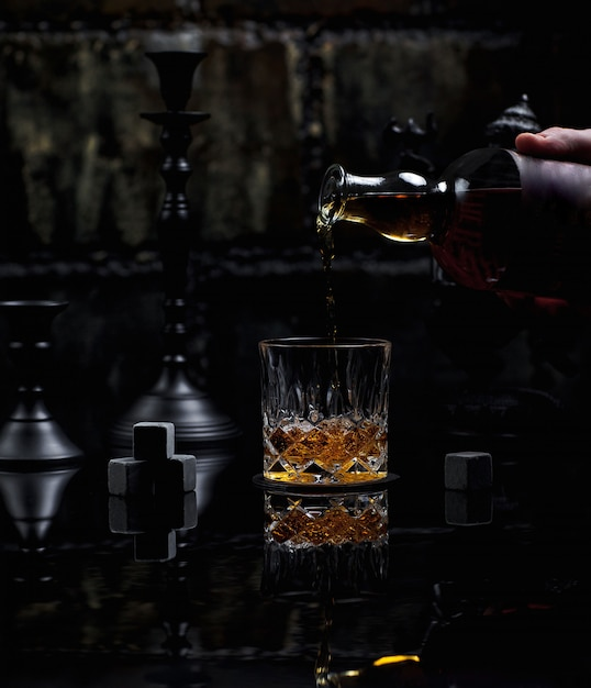 Putting a glass fine blended scotch whiskey Free Photo