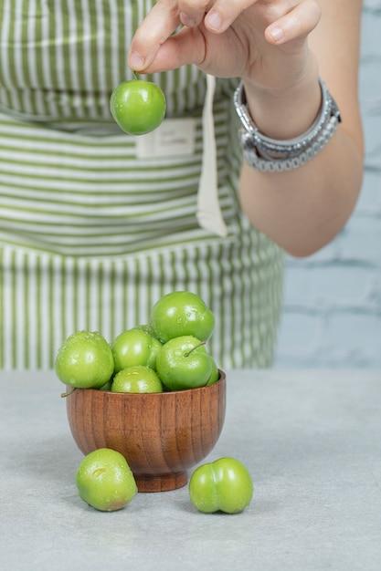 Положить зеленые вишни в деревянную миску Бесплатные Фотографии
