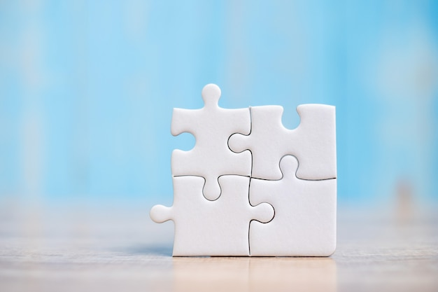 Puzzle pieces on wood table background. business solutions, mission target, successful, goals, cooperation, partnership and strategy Premium Photo