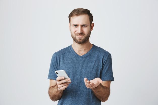 電話でメッセージを読んだ後肩をすくめて困惑して混乱している男 無料写真