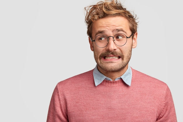 Puzzled attractive bearded emotive man wonk in spectacles, looks with worried embarrassed expression aside Free Photo