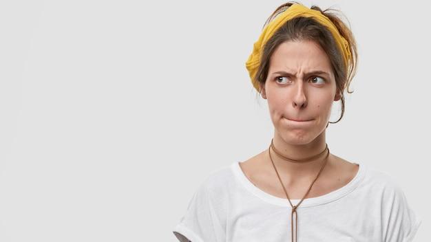 Озадаченная кавказская женщина держит губы сжатыми, выражение лица расстроено, недовольно хмурится, глубоко задумавшись Бесплатные Фотографии