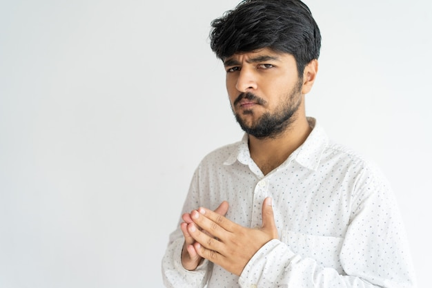 Puzzled concerned indian guy thinking over problem. Free Photo