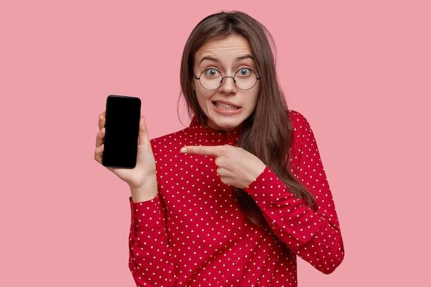 Giovane donna dai capelli scura perplessa con occhiali ottici, punta al gadget elettronico con schermo mock up, indossa una camicia rossa, pubblicizza un nuovo dispositivo, ha gli occhi verdi Foto Gratuite