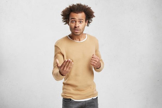 Озадаченный темнокожий мужчина упрекает кого-то и грозит кулаком, носит повседневный свитер Бесплатные Фотографии