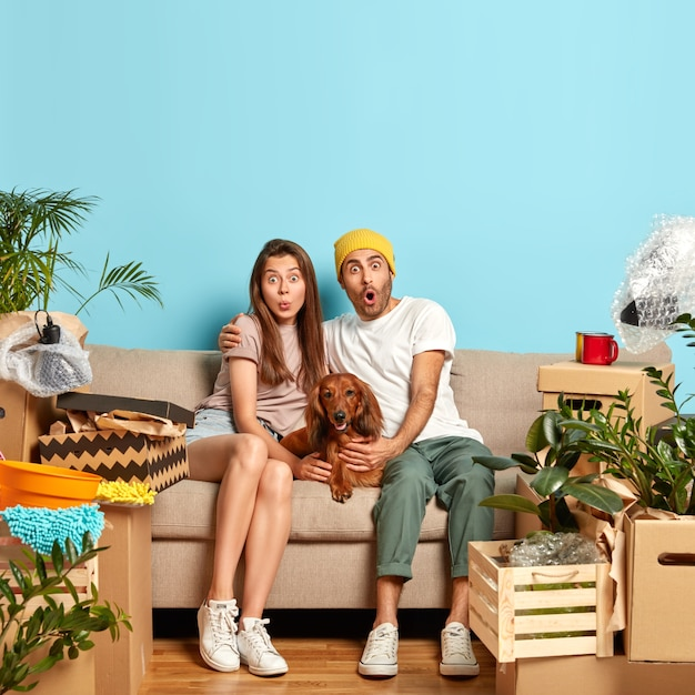 Puzzled family couple sit together near dog on couch, rent new flat, move in apartment, gazes with shock, have day of relocation, surrounded with personal stuff in boxes. new home and moving. Free Photo