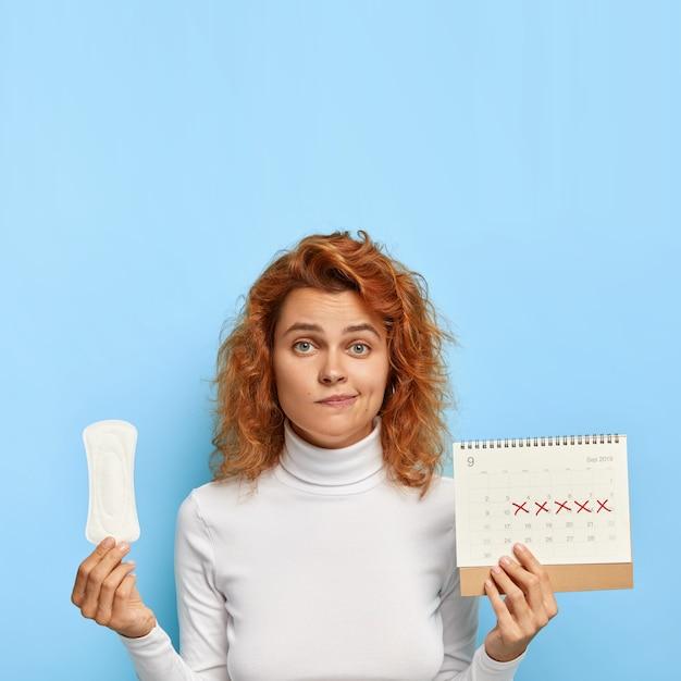 困惑した生姜の女性は、赤い日がマークされた生理用ナプキンと月経カレンダーを保持しています 無料写真