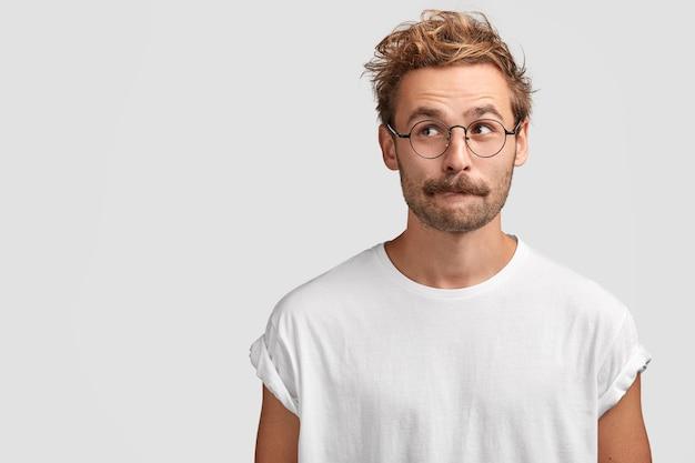 Озадаченный красавец с усами, закусывает нижнюю губу и с любопытством смотрит в сторону, о чем-то думает, одет в повседневную белую футболку, стоит у глухой стены Бесплатные Фотографии